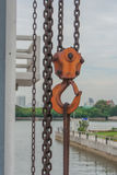 Orange hook hanging on a chain. Stock Photos
