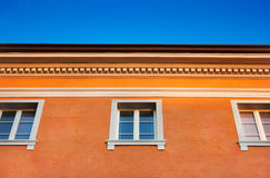 Orange house on blue sky. Orange facade of an old traditional Italian-style building against the blue sky as seen in Italy, Europe stock photo