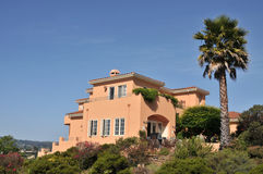 Orange house with large palm tree in back Stock Photos