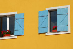 Orange house wall, blue shutters. Orange house wall, two windows, blue shutters royalty free stock photo