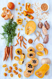 Orange hue toned collection fresh produce. Collection of fresh orange toned vegetables and fruit raw produce on white rustic background, pumpkin butternut carrot Royalty Free Stock Photos