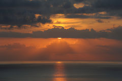 Orange hues sunset with a glimpse of the sun, Tenerife, Canary Islands. Horizontal shot of sunset with patches of dark clouds and sky adorned with brilliant hues Royalty Free Stock Photo