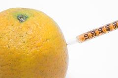 Orange and hypodermic syringe Stock Image