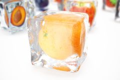 Orange in ice cube  on white with depth of field effects. Ice cubes with fresh berries. Berries fruits frozen in. Ice cubes. 3D rendering Royalty Free Stock Photo