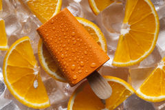 Orange ice lolly and fruits on ice cubes stock images
