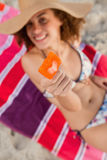 Orange ice lolly held by a young woman while already bitten Royalty Free Stock Photos