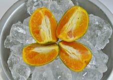 Orange on ice in tin basin Stock Photo