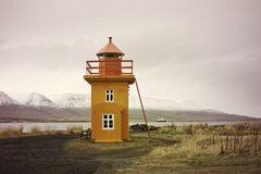 Orange Icelandic Lighthouse against mountain background