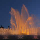Orange illuminated fountain in the evening light of Barcelona Royalty Free Stock Images