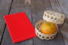 Orange im Korb mit rotem Umschlagpaket oder ANG-Tatze für Geschenk auf altem Hintergrund des hölzernen Brettes Chinesisches Festi Stockbilder
