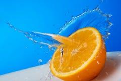 Orange im Spritzenwasser Stockbild