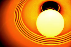 Orange Incandescent Light Bulb. A round orange incandescent light bulb attached to a round lamp shade Stock Photo