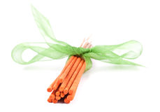 Orange incense sticks with tied with green tie. Isolated on white background Royalty Free Stock Images