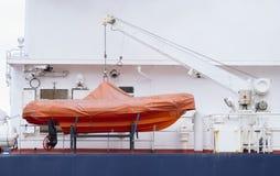 Emergency rescue orange inflatable dinghy boat on ship cruise Royalty Free Stock Image