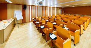 Orange inre konferenskorridorer med flipchart Fotografering för Bildbyråer