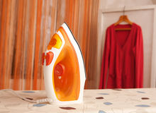 Orange iron on ironing board Royalty Free Stock Image