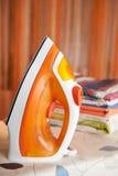 Orange iron on ironing board Royalty Free Stock Photos
