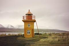 Orange isländsk fyr mot bergbakgrund royaltyfria bilder