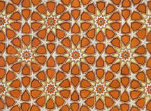Orange Islamic Arabesque Pattern. Very old orange and yellow Islamic arabesque pattern with ornamental flower shaped designs on the ceiling Royalty Free Stock Photos