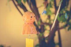 Orange jagende japanische Puppe des Regens, die am Niederlassungsbaum hängt lizenzfreies stockbild