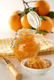 Orange jam. Bottle with orange jam, plate, knife and fresh oranges on back, soft focus Royalty Free Stock Photography