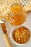Orange jam. Bottle with orange jam, plate, knife and napkin on back Stock Photo