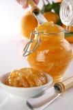 Orange jam. Bottle with orange jam, plate, knife, hand serving and fresh oranges on back, soft focus Stock Image