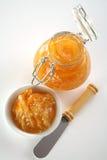 Orange jam. Bottle with Homemade orange jam, plate, and knife Stock Image