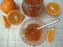 Orange jam and fresh oranges on the table. Stock Photos