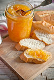 Orange jam in a glass jar and bread Royalty Free Stock Image