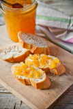 Orange jam in a glass jar and bread Stock Photography