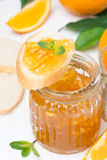 Orange jam in a glass jar and fresh baguette Stock Photos