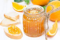 Orange jam in a glass jar and fresh bread Royalty Free Stock Photography