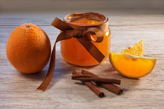 Orange jam in glass jar and oranges on wooden table, front view stock image