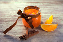 Orange jam in glass jar and pieces of orange on wooden table royalty free stock photography