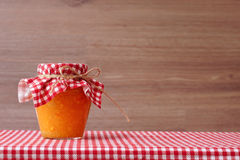 Orange jam in a glass jar on a red checkered tablecloth. Royalty Free Stock Photography