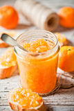 Orange jam in glass jar, tangerines and bread Stock Photography