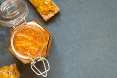 Orange Jam in Jar. Orange jam in swing-top jar, bread slices with orange jam on the side, photographed overhead on slate with natural light (Selective Focus Stock Photography
