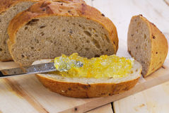 Orange jam and Wholegrain bread. On the wooden table Royalty Free Stock Photography