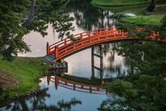 Orange japansk bro i härlig trädgård royaltyfria foton