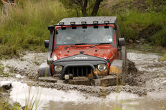 Orange Jeep Rubicon för fruktdryck korsning lerigt damm arkivbild