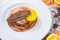 Orange jelly with chocolate on a white plate. Italian dessert with a bar of chocolate. Royalty Free Stock Image