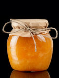 Orange jelly in glass jar isolated on black Stock Photos