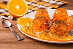 Orange jelly and orange slices with chocolate chips on a white plate, spoon and napkin. On a wooden table royalty free stock image