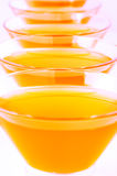 Orange jelly vertical close-up. Orange jelly in glass bowls arranged in a row vertical close-up. on a light background stock photo
