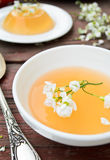 Orange jelly with white flowers on wooden background.  Stock Photo