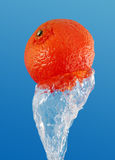 Orange in a jet of water. Royalty Free Stock Photography