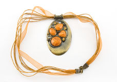 Orange jewelry. Bronze decoration on an orange ribbon with stones Stock Photos