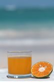 Orange juice. Served in glass on the beach with sea in background Royalty Free Stock Image