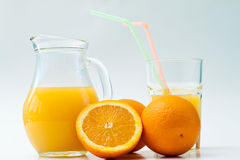 Orange juice. In the jug with oranges Royalty Free Stock Image